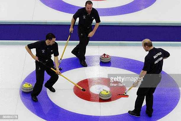 David Murdoch, Warwick Smith, and Ewan MacDonald of Great Britain guide a stone into the house during a preliminary round of men's curling against...