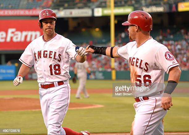 David Murphy and Kole Calhoun of the Los Angeles Angels of Anaheim fist bumping while celebrating after Calhoun scored on a sacrifice fly by Murphy...