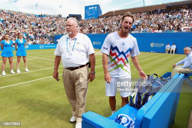 David Nalbandian of Argentina looks on alongside ATP World Tour Supervisor Tom Barnes after learning he is disqualified for unsportsmanlike conduct...