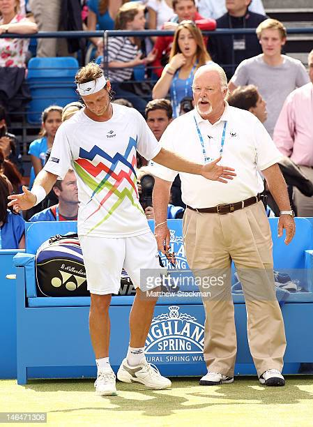 David Nalbandian of Argentina speaks to ATP World Tour Supervisor Tom Barnes after learning he is disqualified for unsportsmanlike conduct during his...