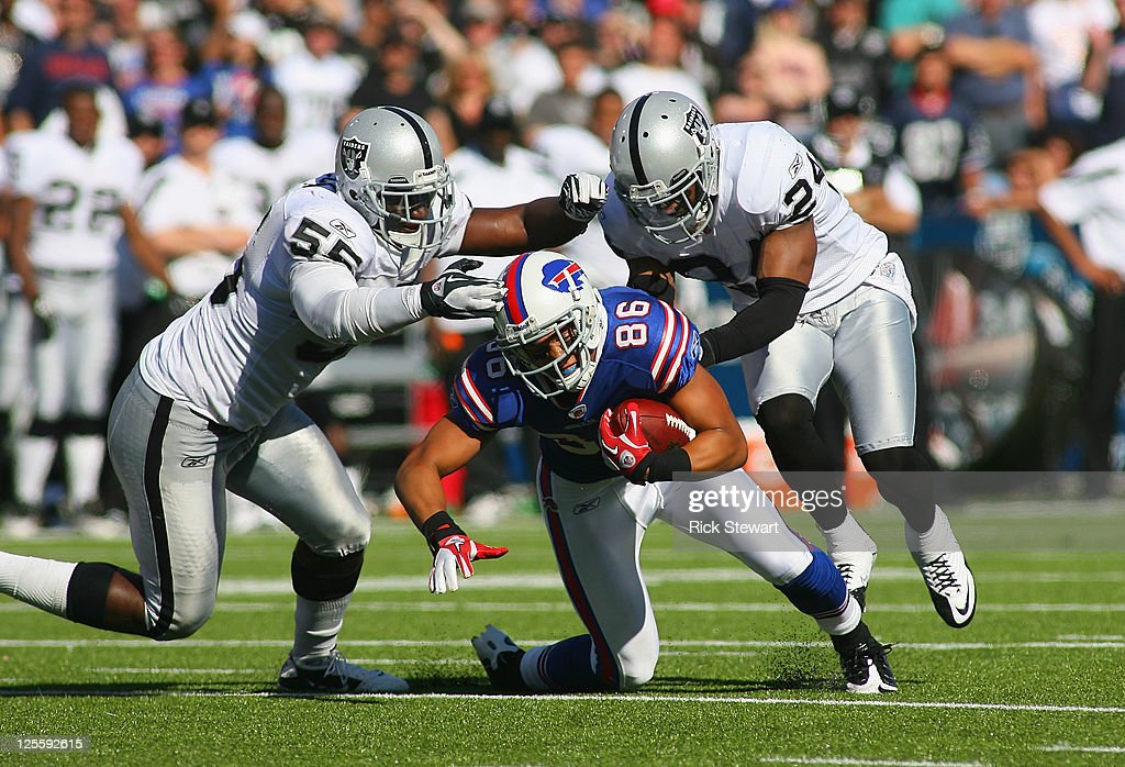 David Nelson #86 of the Buffalo Bills dives forward for a first down as Rolando McClain #55 and Michael Huff #24 of the Oakland Raiders tackle him at Ralph Wilson Stadium on September 18, 2011 in Orchard Park, New York. Buffalo won 38-35.
