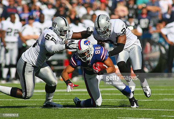 David Nelson of the Buffalo Bills dives forward for a first down as Rolando McClain and Michael Huff of the Oakland Raiders tackle him at Ralph...