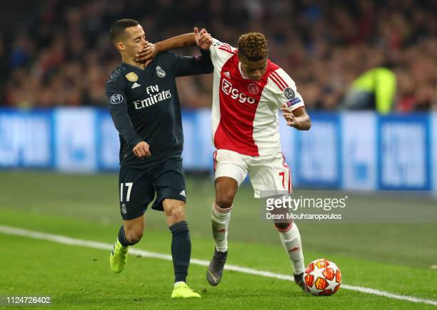 David Neres of Ajax is challenged by Lucas Vazquez of Real Madrid during the UEFA Champions League Round of 16 First Leg match between Ajax and Real...