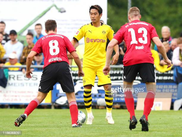David Neuwirth of FC Schweinberg Shinji Kagawa of Borussia Dortmund and Marcel Bund of FC Schweinberg battle for the ball during the preseason...