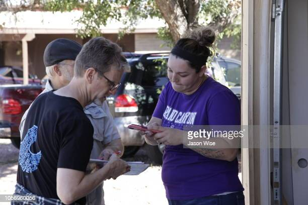 David Nevins and George Rowe of MoveOn speak with Ashley Lira while canvassing for Ann Kirkpatrick on November 3 2018 in Tucson Arizona