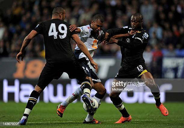 David Ngog of Bolton Wanderers battles for the ball with Younes Kaboul and William Gallas of Tottenham Hotspur during the Barclays Premier League...