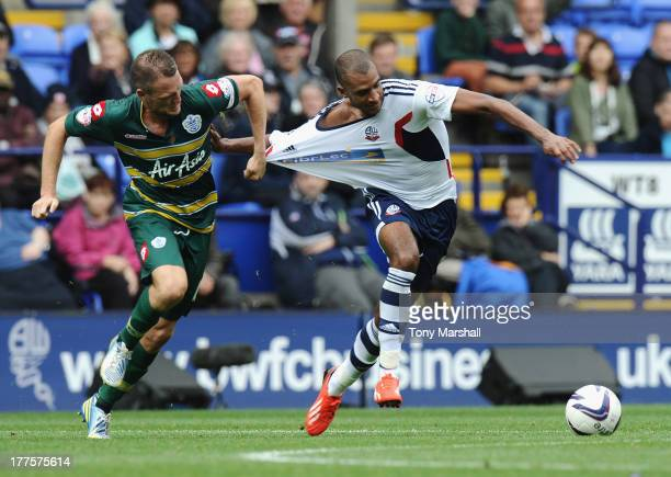 David Ngog of Bolton Wanderers is pulled back by his shirt by Clint Hill of Queens Park Rangers during the Sky Bet Championship match between Bolton...