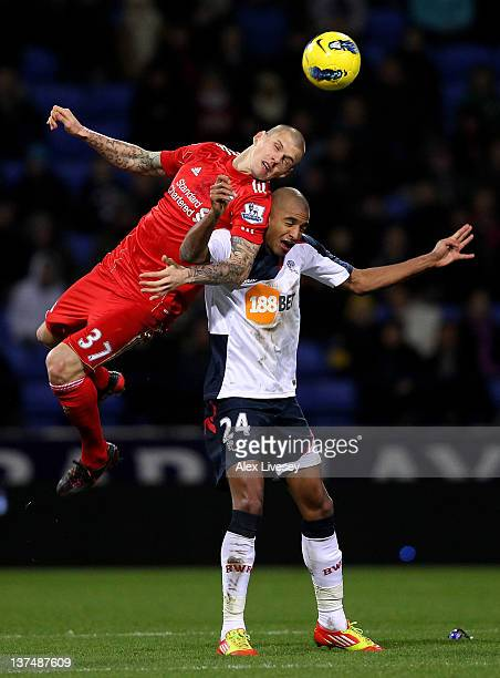 David Ngog of Bolton Wanderers tangles with Martin Skrtel of Liverpool during the Barclays Premier League match between Bolton Wanderers and...