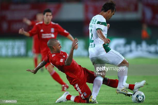David N'Gog of Liverpool challenges Li Zhihai of Guangdong Sunray Cave during the preseason friendly match between Guangdong Sunray Cave and...