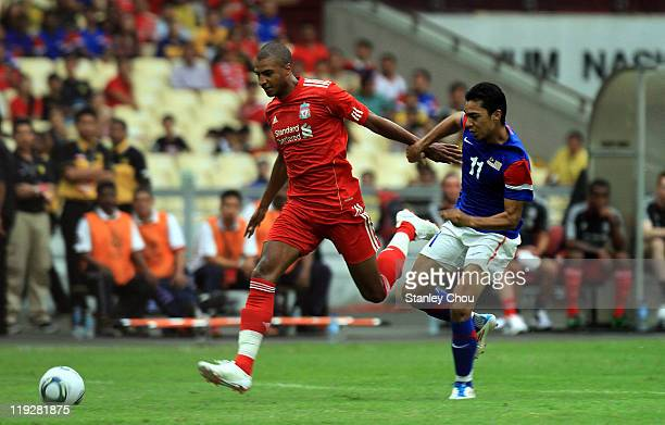 David Ngog of Liverpool is pursuit by Mohd Azmi of Malaysia during the preseason friendly match between Malaysia and Liverpool at the Bukit Jalil...