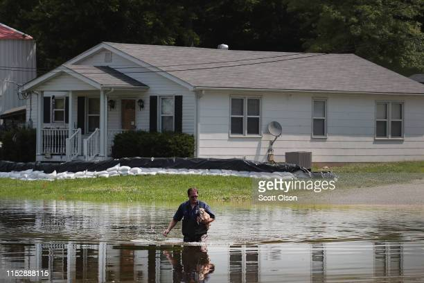 David Nibarger walks through floodwater from the the Mississippi River as he leaves his home with his dog Tiny under his arm on May 31 2019 in...