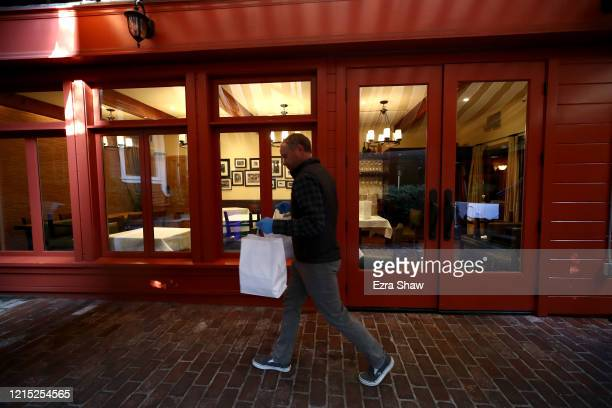 David Nichol the owner of Sociale carries a take out order to the curb March 27 2020 in San Francisco California Sociale is working with a reduced...