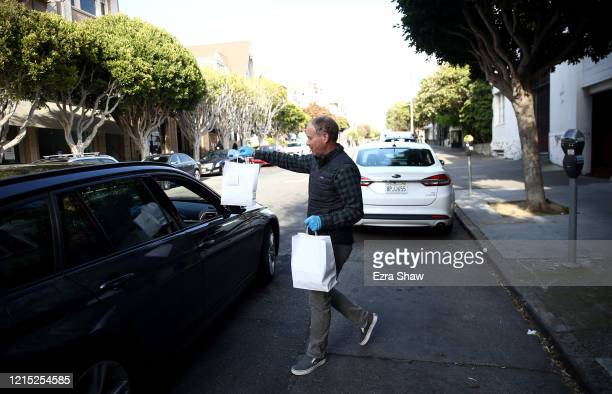 David Nichol the owner of Sociale delivers a meal to a waiting customer on March 27 2020 in San Francisco California Sociale is working with a...