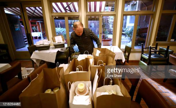 David Nichol the owner of Sociale prepares dinners for delivery in his empty dining room on March 27 2020 in San Francisco California Sociale is...