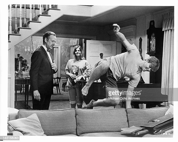 David Niven and Cristina Ferrare watch as Rick Chalet jumps over the sofa in a scene from the film 'Impossible Years' 1968
