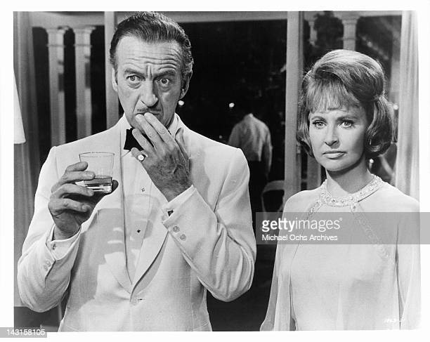 David Niven and Lola Albright stand looking perplexed in a scene from the film 'Impossible Years' 1968