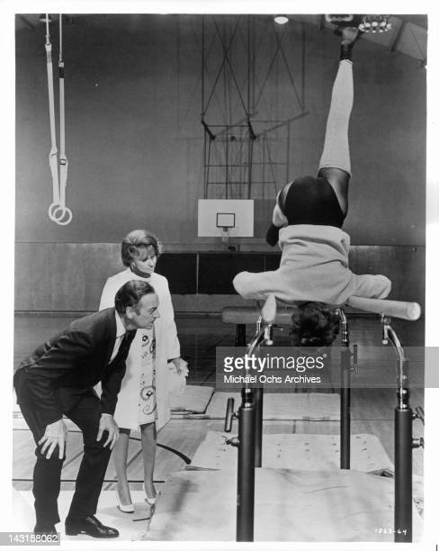David Niven and Lola Albright try to identify who is upside down on the bars in a scene from the film 'Impossible Years' 1968