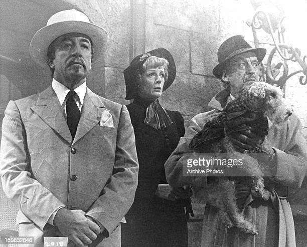 David Niven holding an Airedale dog with Maggie Smith and Peter Sellers in a scene from the film 'Murder By Death' 1976