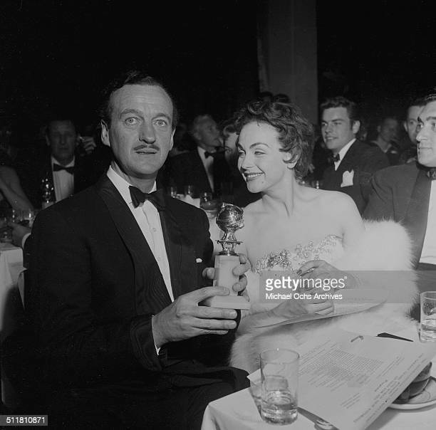 David Niven with his wife Hjordis Genberg pose with his Golden Globe Award for Best performance by an actor in a motion picture in The Moon is Blue...