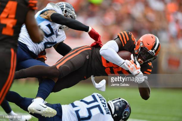 David Njoku of the Cleveland Browns is brought down after a catch in the first quarter by Kenny Vaccaro of the Tennessee Titans and Adoree' Jackson...