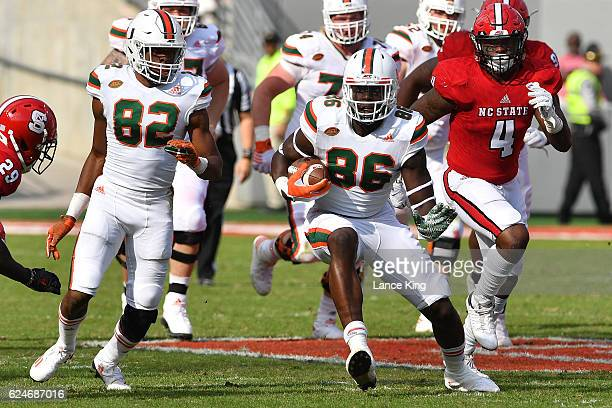 David Njoku of the Miami Hurricanes runs with the ball against the North Carolina State Wolfpack at CarterFinley Stadium on November 19 2016 in...