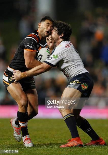 David Nofoaluma of the Tigers and Jake Granville of the Cowboys clash heads in a tackle during the round 20 NRL match between the Wests Tigers and...