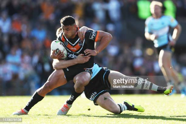 David Nofoaluma of the Tigers Is tackled by Kurt Capewell of the Sharks during the round 25 NRL match between the Wests Tigers and the Cronulla...