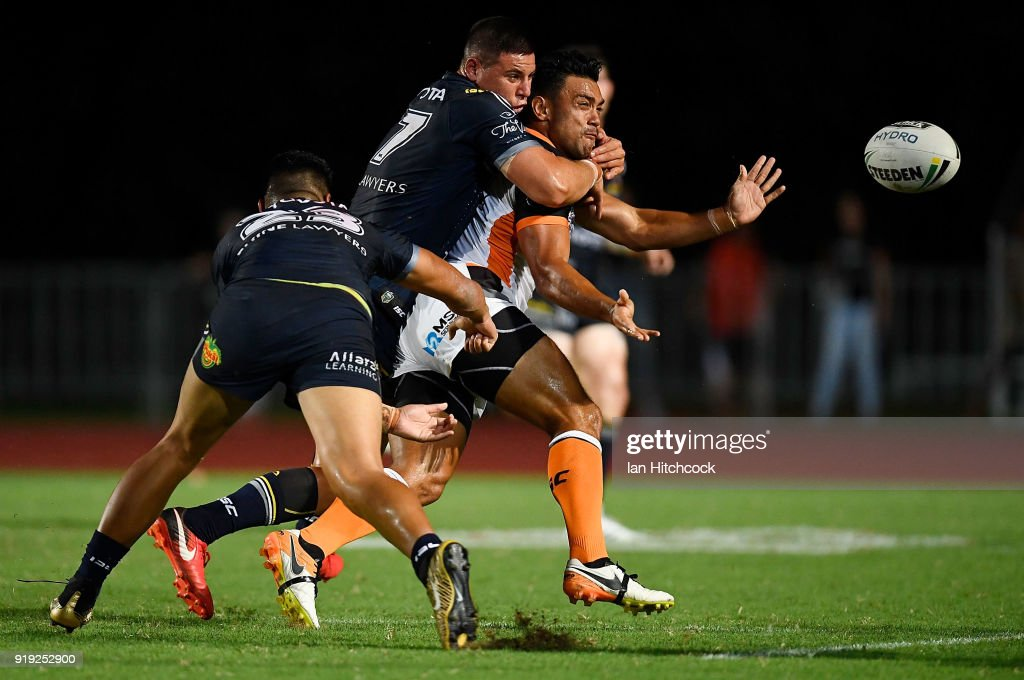 David Nofoaluma of the Tigers is tackled by Murray Taulagi and Shane Wright of the Cowboys during the NRL trial match between the North Queensland Cowboys and the Wests Tigers at Barlow Park on February 17, 2018 in Cairns, Australia.
