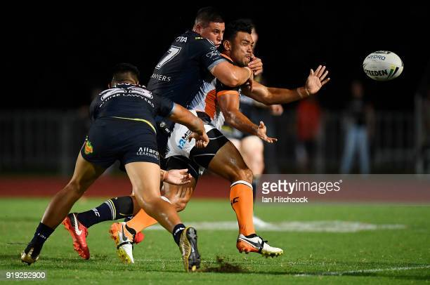 David Nofoaluma of the Tigers is tackled by Murray Taulagi and Shane Wright of the Cowboys during the NRL trial match between the North Queensland...