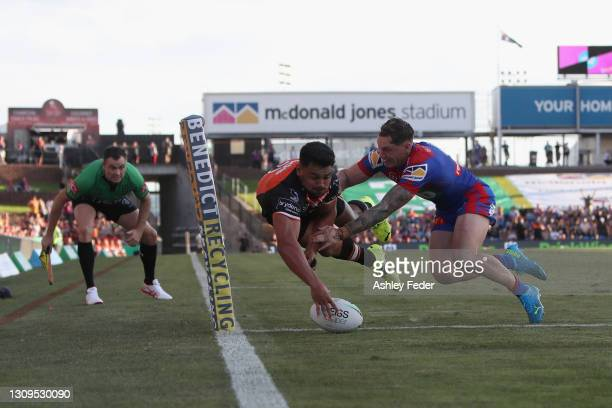 David Nofoaluma of the Tigers scores a try defended by Kurt Mann of the Knights during the round three NRL match between the Newcastle Knights and...