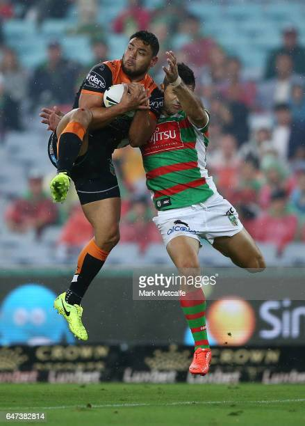 David Nofoaluma of the Tigers takes a high ball ahead of Alex Johnston of the Rabbitohs during the round one NRL match between the South Sydney...