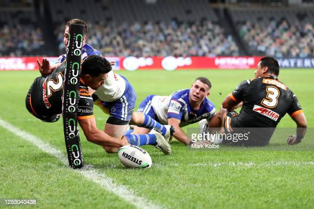 David Nofoaluma of the Wests Tigers scores a try as he is tackled by Kieran Foran of the Bulldogs during the round seven NRL match between the...