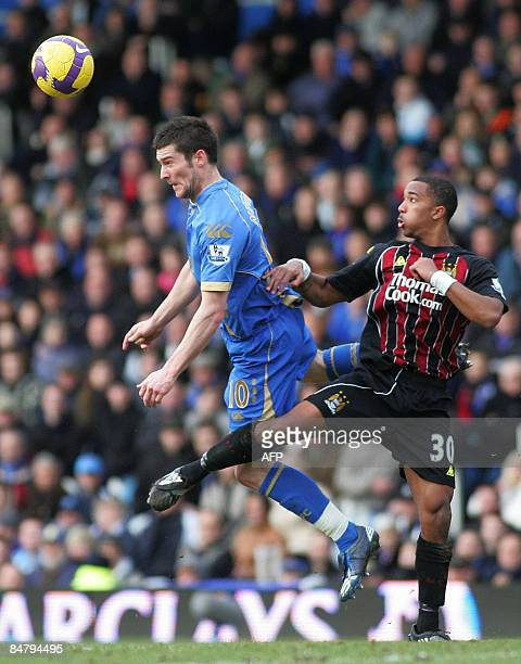 David Nugent of Portsmouth and Shaleum Logan of Manchester City battle for the ball during the Premier League football match between Portsmouth FC...