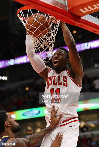 David Nwaba of the Chicago Bulls dunks over Perry Jones of the New Orleans Pelicans during a preseason game at the United Center on October 8 2017 in...