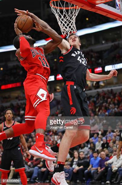 David Nwaba of the Chicago Bulls is fouled by Jakob Poeltl of the Toronto Raptors at the United Center on February 14 2018 in Chicago Illinois The...