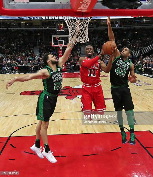 David Nwaba of the Chicago Bulls puts up a shot between Abdel Nader and Al Horford of the Boston Celtics at the United Center on December 11 2017 in...