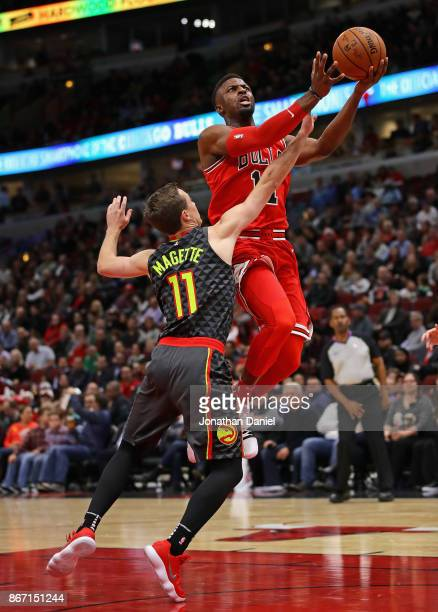 David Nwaba of the Chicago Bulls puts up a shot over Josh Magette of the Atlanta Hawks at the United Center on October 26 2017 in Chicago Illinois...