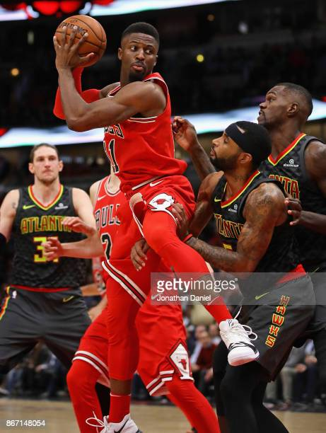 David Nwaba of the Chicago Bulls rebounds over Malcolm Delaney of the Atlanta Hawks at the United Center on October 26 2017 in Chicago Illinois The...