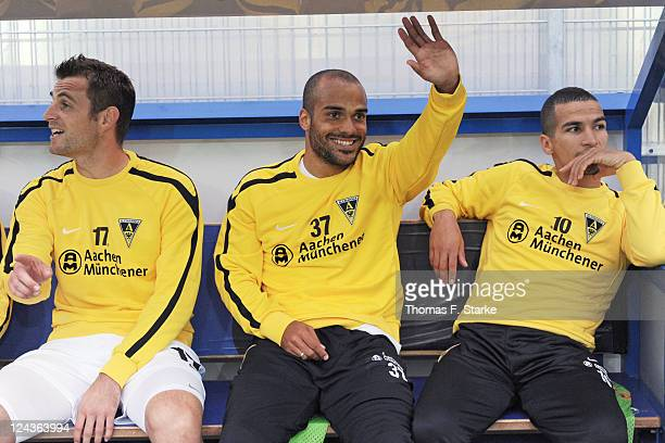 David Odonkor of Aachen greets sitting on the substitutes bench between Thomas Stehle and Anouar Hadouir prior to the Second Bundesliga match between...