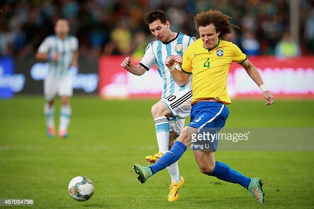 David of Brazil competes the ball with Lionel Messi of Argentina during Super Clasico de las Americas between Argentina and Brazil at Beijing...