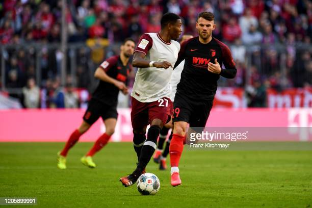 David Olatukunbo Alaba of Bayern Muenchen and Eduard Loewen of FC Augsburg during the Bundesliga match between FC Bayern Muenchen and FC Augsburg at...