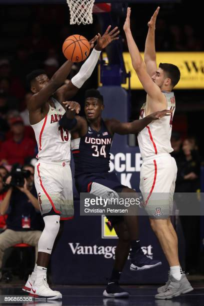 David Onuorah of the Connecticut Huskies passes the ball under pressure from Deandre Ayton and Dusan Ristic of the Arizona Wildcats during the first...