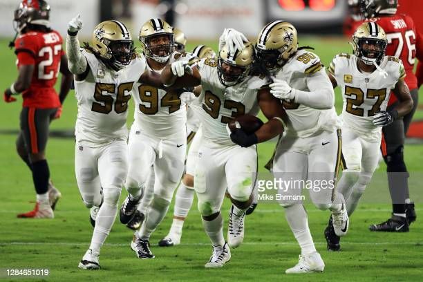 David Onyemata of the New Orleans Saints celebrates with teammates after intercepting a pass during the second quarter against the Tampa Bay...