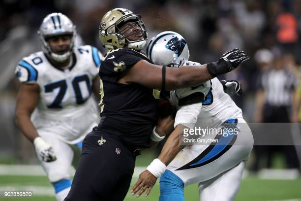David Onyemata of the New Orleans Saints tackles Cam Newton of the Carolina Panthers at the MercedesBenz Superdome on January 7 2018 in New Orleans...