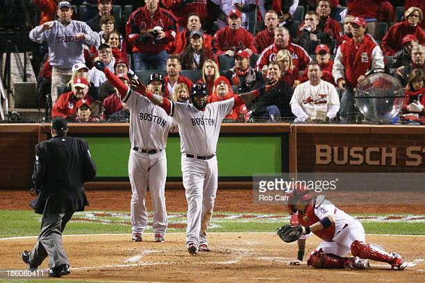 David Ortiz and David Ross of the Boston Red Sox celebrate after Ortiz scored on a sacrifice fly to left field hit by teammate Stephen Drew against...