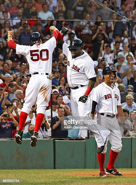 David Ortiz high fives Mookie Betts of the Boston Red Sox after hitting a threerun home run in the third inning during the game against the Detroit...