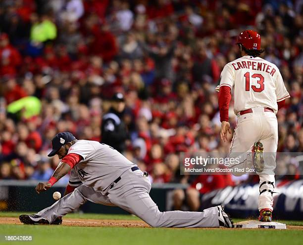 David Ortiz of the Boston Red Sox can't handle a poor throw as Matt Carpenter of the St Louis Cardinals reaches first base in the seventh inning of...