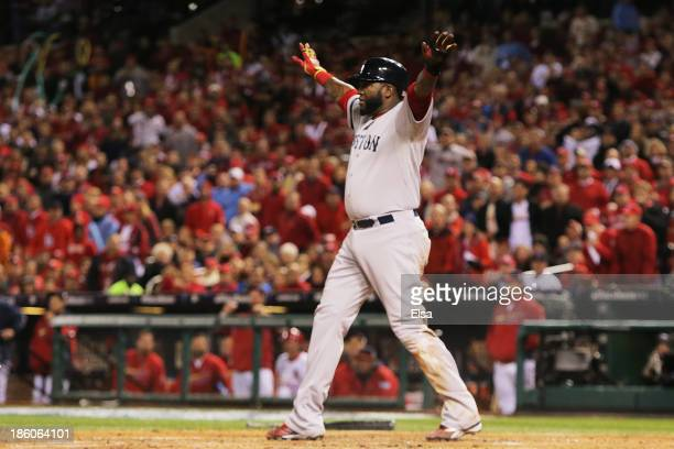 David Ortiz of the Boston Red Sox celebrates scoring a run after sliding safe into home plate on a sacrifice fly to left field hit by teammate...