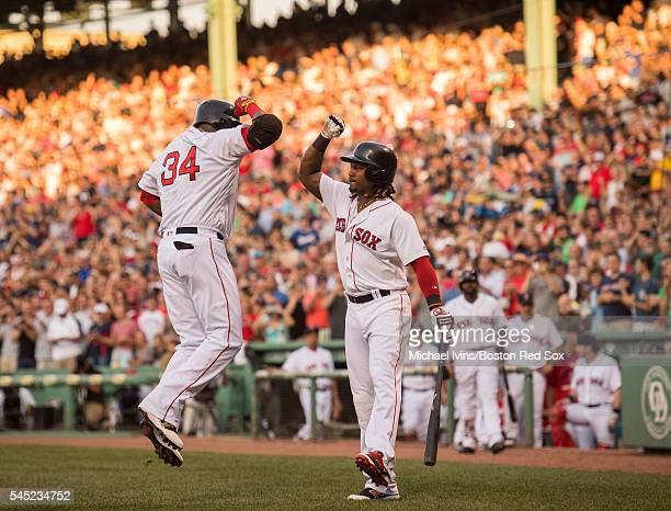 David Ortiz of the Boston Red Sox celebrates with Hanley Ramirez after hitting a tworun home run against the Texas Rangers in the first inning on...