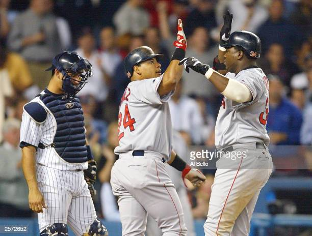 David Ortiz of the Boston Red Sox celebrates with teammate Manny Ramirez after hitting a tworun home run in the top of the forth inning against the...